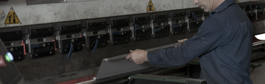 GSI staff operating a press for folding sheetmetal. Industrial Engineering.